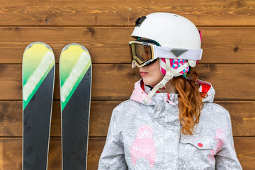 portrait woman skier with skis and helmet near wooden wall