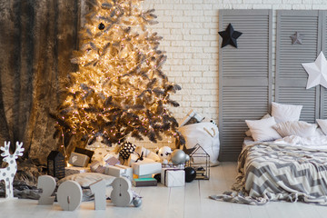 New Year decorated modern interior bedroom with Christmas tree and stars. Scandinavian design room