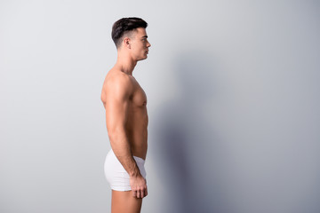 Side view photo of handsome condifend guy wearing white underwear and staying still against grey background