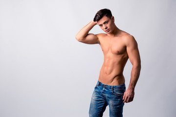 Portrait of handsome confident sportive muscular athletic with rock-hard pecs guy clothed in jeans, he is posing against grey background, copy-space