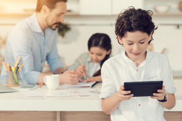 Modern igen. Nice positive smart boy smiling and looking at the tablet screen while using it for plying games