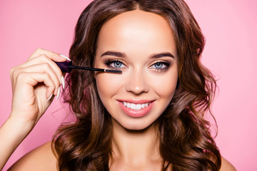 Close up cropped shot of adorable fresh attractive gorgeous charming lady with ideal face, healthy shiny clear skin, amazing hairstyle, tube of mascara in arm. Pampering, skincare perfection