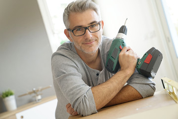Portrait of cheerful man with electric drill
