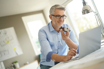 Architect in office talking to client with smartphone