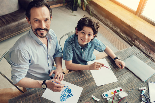 Creative outlet. Joyful positive creative father and son sitting together and looking at you while sitting together