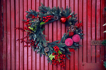 pine garland for Christmas hanging on red wooden wall