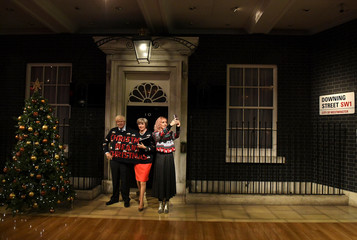 A woman poses next to Madame Tussauds' wax figures of Britain's Prime Minister Theresa May and Foreign Secretary Boris Johnson wearing one Christmas themed jumper between them and holding a sign, in London