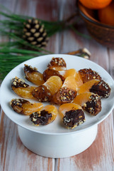 Mandarin in chocolate glaze and nuts on the table