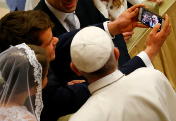 A newly-wed couple takes a selfie with Pope Francis during his Wednesday general audience in Paul VI Audience Hall at the Vatican