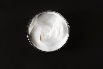 Jar of cream for the face. Copy space. Black background.