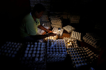 A worker checks eggs in front of a bulb inside a wholesale egg shop at a market in Kolkata