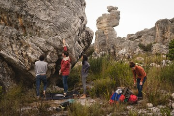 Friends examining cliff