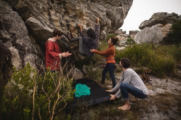 Friends assisting man in rock climbing