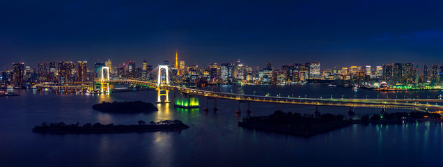 Panorama of tokyo cityscape and rainbow bridge at night.