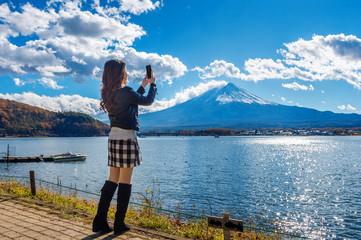 Wall Mural - Woman use mobile phone take a photo at Fuji mountains, Kawaguchiko lake in Japan.