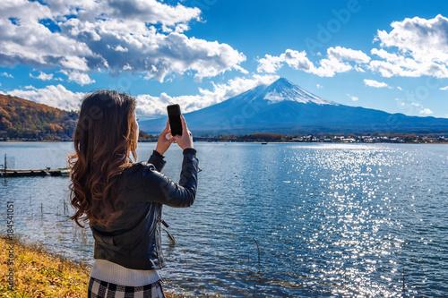 Wall mural Woman use mobile phone take a photo at Fuji mountains, Kawaguchiko lake in Japan.