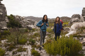 Portrait of female friends standing with rucksack