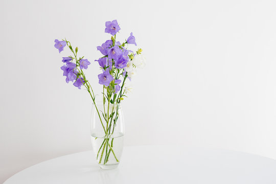 Flowers bells in a glass vase stand on a white round table