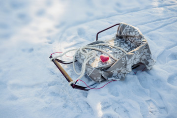Sledges covered warmth wool plaid outdoor in winter on the snow and red heart shape. Care and safety concept