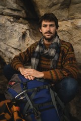 Confident man with rucksack relaxing on rock