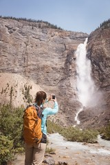 Female hiker taking picture of waterfall with mobile phone