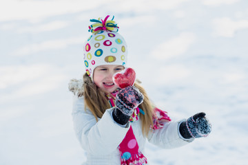 Little girl shows heart outdoor in winter. Save warmth