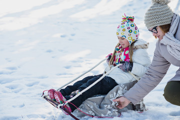 Mother and daughter sledging in winter park