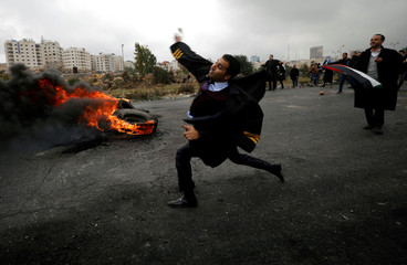 A Palestinian lawyer hurls stones towards Israeli troops during clashes at a protest near the Jewish settlement of Beit El, near the West Bank city of Ramallah