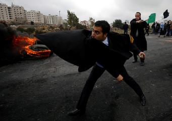 Palestinian lawyer hurls stones towards Israeli troops during clashes at a protest near the Jewish settlement of Beit El, near the West Bank city of Ramallah