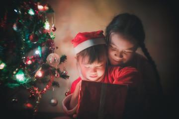 Little Girl in santa costum opens a gift for Christmas
