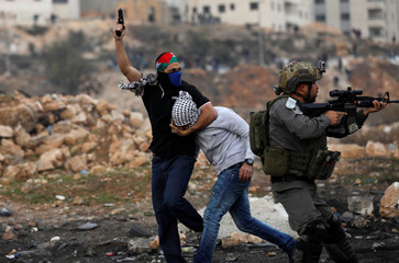 An undercover Israeli security personnel detains a Palestinian demonstrator during clashes at a protest near the Jewish settlement of Beit El, near the West Bank city of Ramallah
