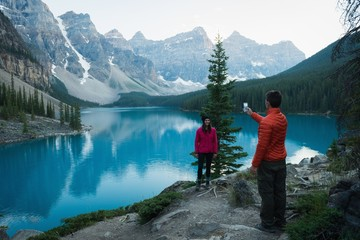 Man taking picture of woman with mobile phone