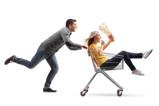 Young man pushing a shopping cart with a woman with a popcorn box riding inside