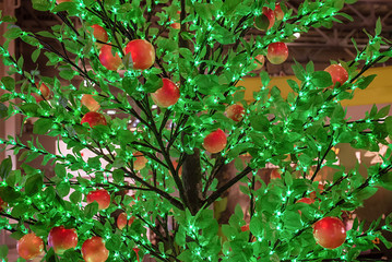 LED decorative lighting. Fruit tree with green leaves and red apples.