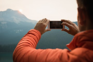 Hiker taking a picture with his mobile phone