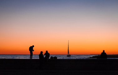 Silhouettes of several people and yacht with a big sail on the seaat the night