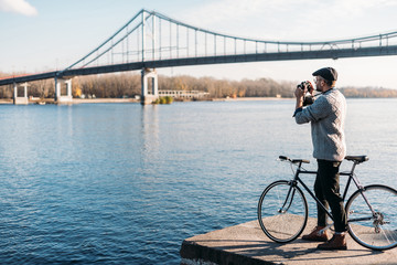 handsome man with vintage film camera and bike standing on river shore