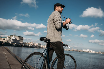 stylish man with vintage film camera and bike standing on river shore