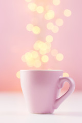Pink coffee cup with lights bokeh
