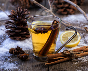 Hot winter beverage with cinnamon, anise and lemon. Winter scene with pine cones and snow.