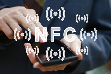 Payment in a trade with nfc system with mobile phone. Businessman hand press button NFC on phone.