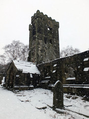 the ruined medieval church in heptonstall with graveyard in the snow showing porch and bell tower