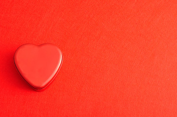 Valentine's Day. A red heart shape tin isolated on a red background