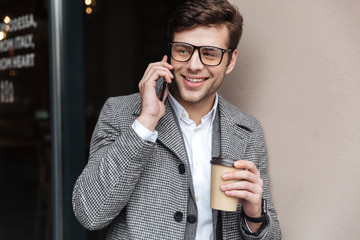 Pleased business man in eyeglasses and coat talking by smartphone