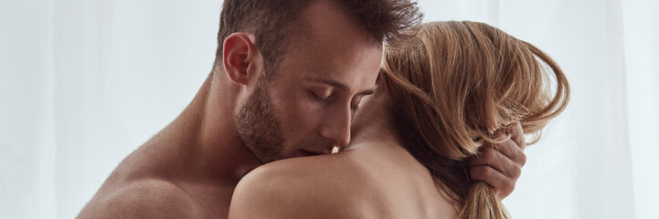 Man kissing woman's collarbone