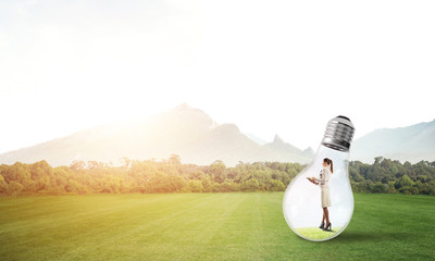 Businesswoman inside light bulb