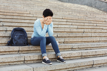 Desperate student sitting on stairs outdoors
