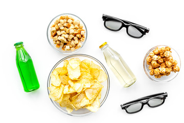 Fast food for watching film. Crisps, popcorn, rusks near drink and glasses on white background top view