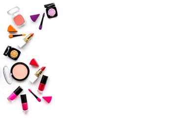 Makeup set pattern. Eyeshadows, rouge, nailpolish, lipstick, applicators on white background top view copyspace