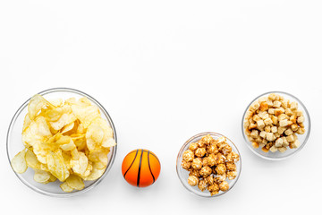Snacks for watching sport matches and games on TV. Crisps, popcorn, rusks near ball on white background top view copyspace